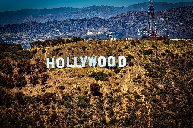 A sign with Hollywood Sign in the background